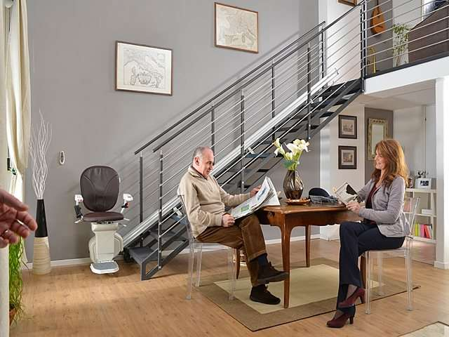 Male and female users seated at table reading paper newspapers next to brown coloured Platinum Horizon stair lift parked at bottom of stairs.