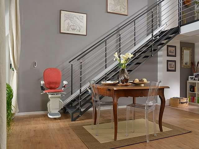 Red coloured Platinum Horizon stair lift parked at bottom of stairs.