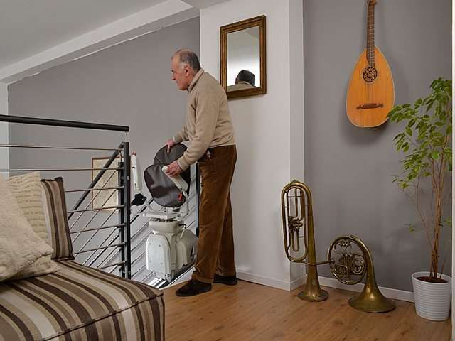 Male user standing on top of stairs landing next to dark coloured upholstery Platinum Horizon stair lift lifting up seat, handrails, and stair lift footrest.