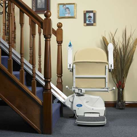 Front view of beige-coloured Handicare Simplicity 950 stair lift parked at the bottom of straight stairs, with armrests, seat, and footrest all in the up position.