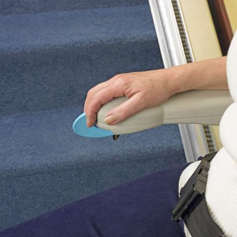 A close-up view of the arm rest toggle control on the Handicare Simplicity 950 series stair lift. The user's hand is shown operating the stair lift toggle switch control.