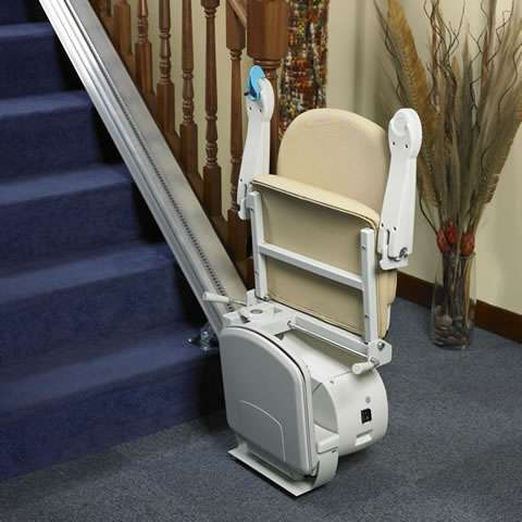 Angled side view of beige-coloured Handicare Simplicity 950 stair lift parked at the bottom of straight stairs, with armrests, seat, and footrest all in the up position, to illustrate how much spare walking space is available for people to use.