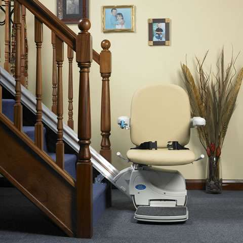 Front view of beige-coloured Handicare Simplicity 950 stair lift parked at the bottom of straight stairs, with arm rests, seat, and foot rest all in the down position, so the stairlift is ready to use.