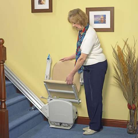 Front view of beige-coloured Handicare Simplicity 950 stair lift parked at the bottom of straight stairs, while a female user is moving the seat position from Up to the Down position. The arm rests and foot rest are still in the Up position.