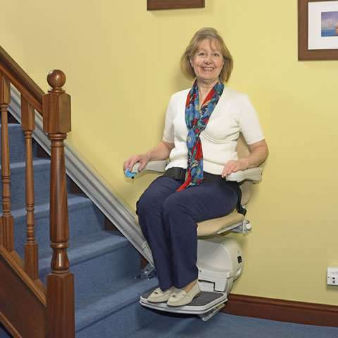 Front view of smiling female user sitting on a beige-coloured Handicare Simplicity 950 stair lift. With hand on armrest control, the user is driving the stairlift to go up the straight stairs.