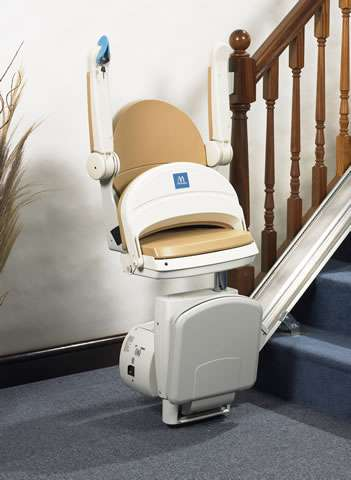 With the same opposite angled front-to-side view of beige-coloured Handicare Simplicity 950 stair lift as shown in the previous photo, the Handicare Simplicity 950 series stairlift is parked at the bottom of straight stairs, with armrests, seat, and footrest all in the up position, to further describe how much walking space around the base of the stairs is therefore made available.