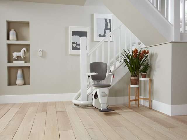 A grey coloured upholstery Flow stair lift parked neatly at the bottom of the stairs around a curve to keep the stairs area as clear as possible. The stairlift chair seat, armrests and footrest are all down, so the stairlift is ready for use.