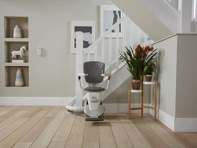 A wider angle view photo of a grey coloured upholstery Flow stair lift parked neatly at the bottom of the stairs around a curve to keep the stairs area as clear as possible. The stairlift chair seat, armrests and footrest are all down, so the stairlift is ready for use.