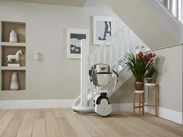Taken from a different angle to the previous photo. A grey coloured upholstery Flow stair lift parked neatly at the bottom of the stairs around a curve to keep the stairs area as clear as possible. The stairlift chair seat, armrests and footrest are all up, showing how little space the chair takes up when not required.