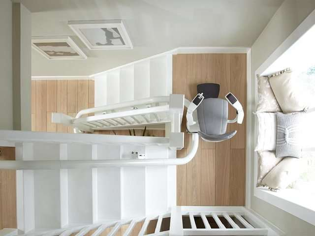 A bird's eye view photo of a grey upholstery Flow stairlift positioned at the mid-way landing position of curved, angled staircase.