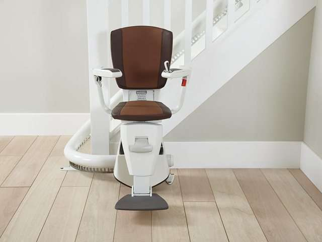 A photo of a two-tone brown upholstery Flow stair lift as it is parked at the bottom of the stairs around the curve, to provide free access to the stairs for people who do not need the use of the stairlift. The stair lift chair seat, armrests, and footrest are all in the down position.