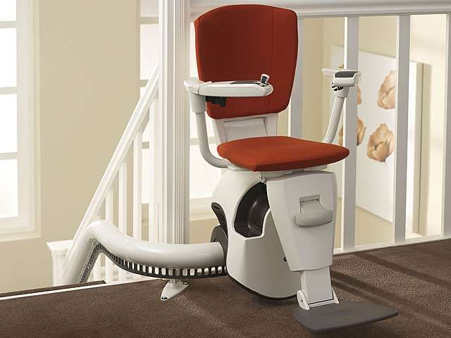 A red coloured Flow stair lift shown situated at the top of the stairs and parked around another curve safely facing the landing area, with seat, armrests, and footrest all in the down position, ready for use.