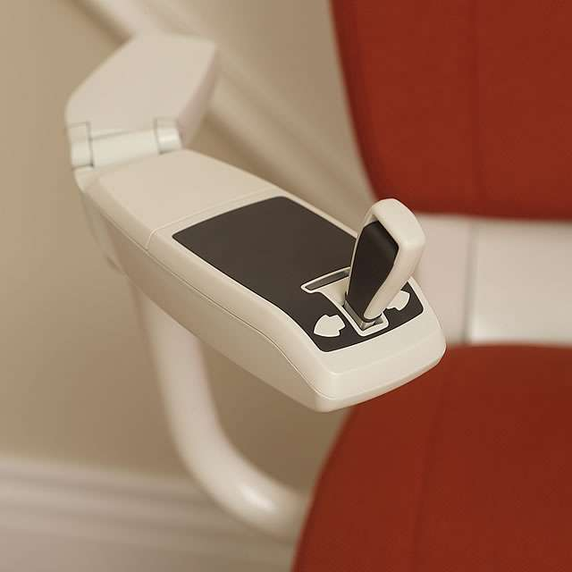 A close-up photo of the red Flow stairlift armrest joystick control.