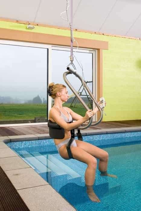 A mostly side view of Handi-Move pool ceiling mobility hoist sling showing female user sitting in sling as she is lowered into the pool water by an operator.