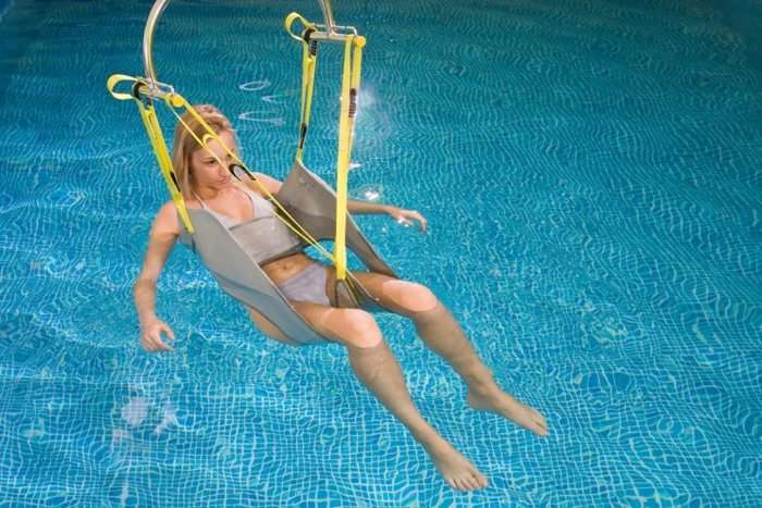 A mostly front view of Handi-Move pool ceiling mobility hoist sling showing female user in sling as lowered into the pool water.