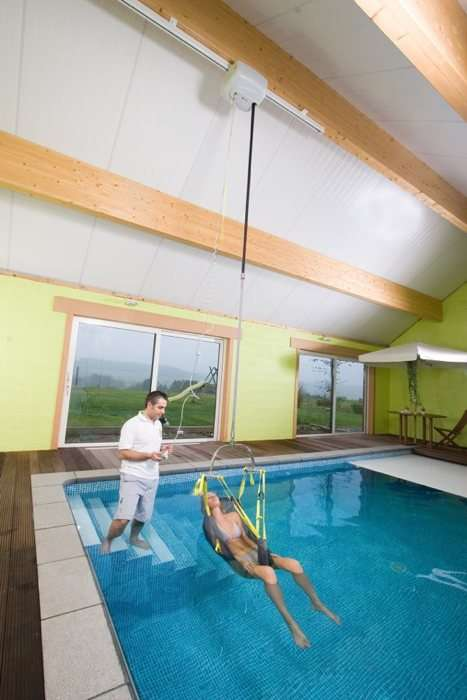 Handi-Move pool ceiling mobility hoist sling showing operator using hand control to lower female user into the pool.