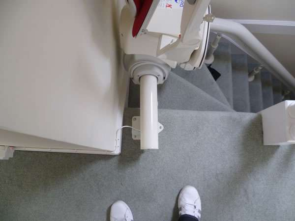 Otolift stairlift installation, red upholstery, stair lift at the top of curved stairs facing the landing with seat, armrests and footrest all in the folded up position. Close-up view of how the power is connected to the stair lift rail