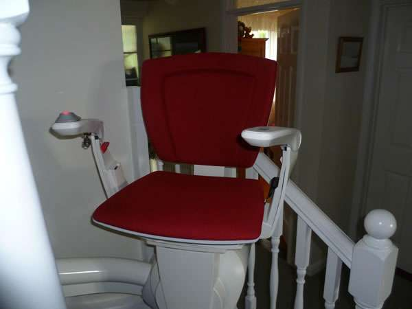 Otolift stairlift installation, red upholstery, with stair lift parked near the bottom of the stairs with seat, arm rests, and foot rest all opened out in the down position