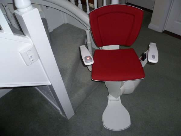 Otolift stairlift installation, red upholstery, showing the stair lift parked at the bottom of the stairs with seat, arm rests, and foot rest all opened out in the down position
