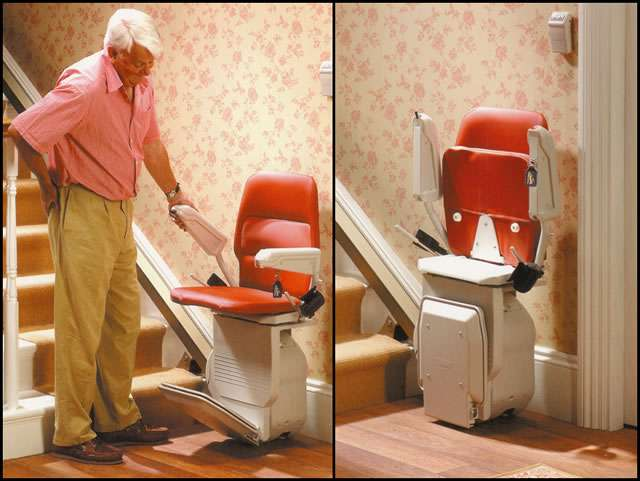 A 2-part composite front-to-side angle image of Stannah Saxon 420 stair lift with red upholstery parked at the bottom of straight stairs. The left side image shows male user standing next to the stairlift and lifting one of the armrests. The right side image shows the Stannah Saxon 420 stair lift with red upholstery parked at the bottom of the stairs with the arm rests, seat, and foot rest all in the up position, allowing for maximum walkspace near the stairlift and bottom of staircase.