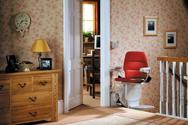 A Stannah Saxon 420 stair lift with red upholstery is shown at the top of the stairs with the chair facing inwards toward the landing area. Positioned in this way, the stairlift can also act as a safety barrier across the stairs.