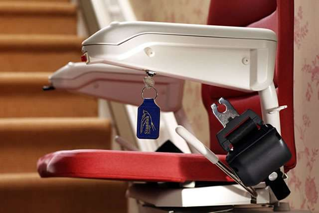 A close-up side view of the Stannah Saxon 420 stairlift seat and armrests area. The seat belt is undone and there is a key inserted into the lower side of one of the arm rests. The stairlift has red coloured upholstery.