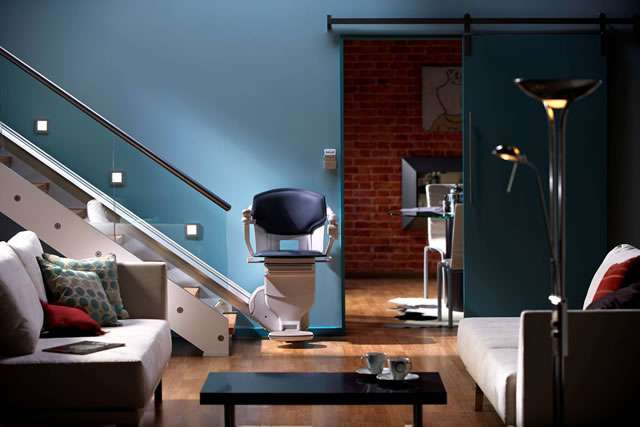 A front facing photo of a dark blue coloured Stannah Solus 420 stairlift shown parked at the bottom of the straight stairs, with seat, armrests, and footrest all in the down position.