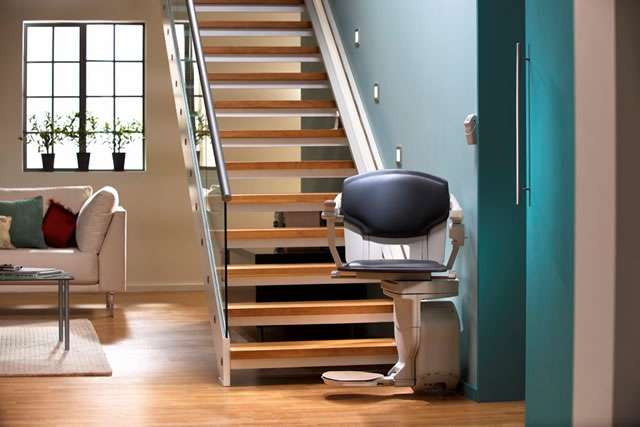 A photo of the Stannah Solust 420 stair lift parked at the bottom of the straight stairs, with the stairlift chair swivelled to face the camera. The armrests, seat, and footrest are all in the down position, so the stair lift is ready for use.