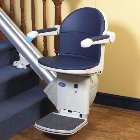 A mostly front view photo of a blue coloured Handicare 1000 series stair lift parked at the bottom of a straight staircase, with armrests, seat, and footrest all in the down position.