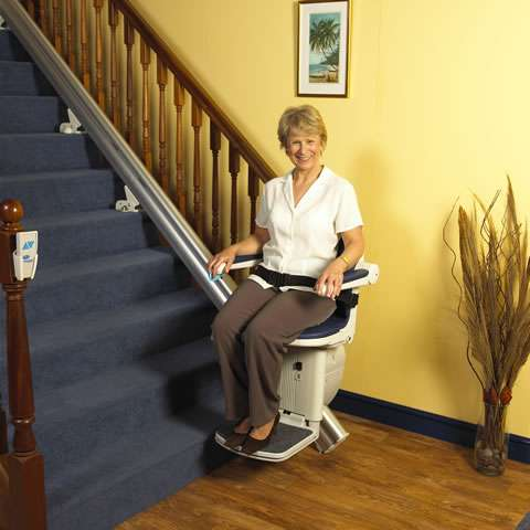 A mostly front view photo of a smiling female user sitting on a blue coloured Handicare 1000 series stair lift parked at the bottom of straight stairs, with armrests, seat, and footrest all in the down position, and seatbelt on.