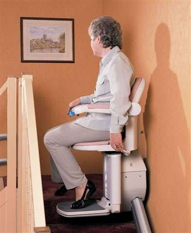 A side view of a female user sitting on a Handicare 1000 series stairlift as it arrives at the top-of-stairs landing area.