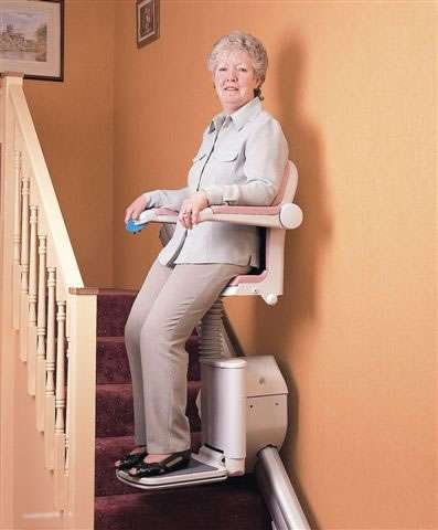 A mostly front-to-side angle view of a smiling female user on a Handicare Stand and Perch stairlift riding up or down straight stairs.