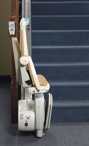 A full side view of beige-coloured Handicare Simplicity 950 stair lift parked at the bottom of straight stairs, with armrests, seat, and footrest all in the up position, to illustrate how much spare walking space is available for people to use.