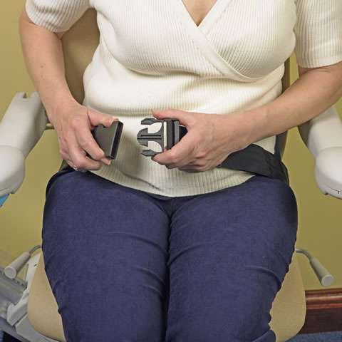 A close-up photo of a female user putting on the seatbelt while sitting on a Handicare Simplicity 950 series stair lift.