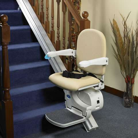 Angled side view of beige-coloured Handicare Simplicity 950 stair lift parked at the bottom of straight stairs, with armrests, seat, and footrest all in the down position, so the stairlift is ready to use.