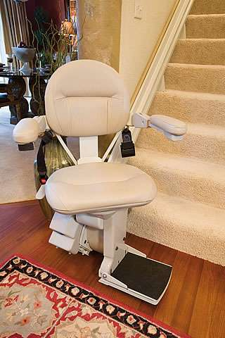 Angled view from further back of cream-coloured Homeadapt Elite stairlift parked at the bottom of the stairs. Arm rests, seat, and foot rest are in the down position.