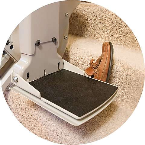 A close-up view of the Homeadapt Elite stairlift footrest as the stair lift travels up the stairs and is then automatically paused as the foot rest comes into contact with a single shoe dropped onto a stair.
