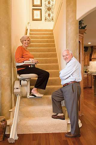 Front view photo of smiling female user riding up straight stairs using a Homeadapt Elite stair lift. Smiling male user standing at the bottom of the stairs facing the camera.