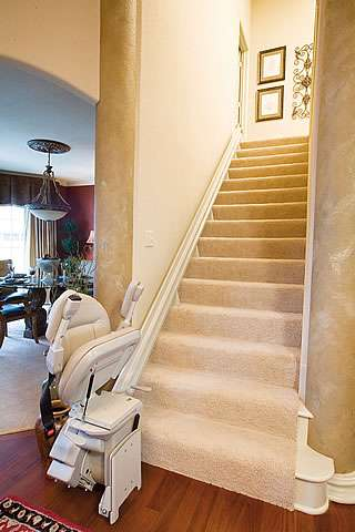 View of a cream coloured Homeadapt Elite stairlift parked at the bottom of straight stairs, with armrests, seat, and footrest all in the up position, to allow maximum space for people who do not require use of the stairlift to walk up and down the stairs.