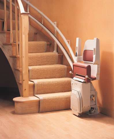 The Stannah Sarum 260 curved stair lift in red shown parked at the bottom of the stairs. The armrests, seat, and footrest are all shown in the up position.
