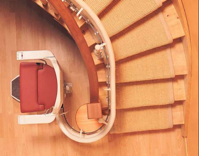 A bird's eye view looking down directly on top of the Stannah Sarum 260 series red stairlift. The photo shows the extreme curve that the stair lift design can handle, with the stairlift rail running near the inner / bannister side.