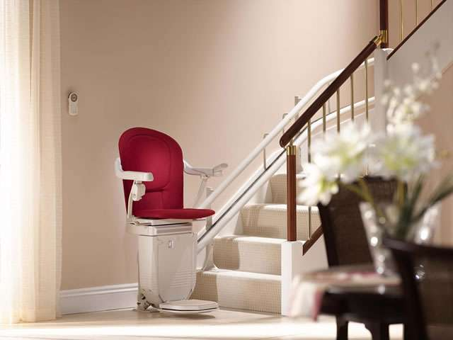 Stannah 260 series Sofia stair lift in red parked at the bottom of curved stairs. Seat, armrests and footrest all in the down position.