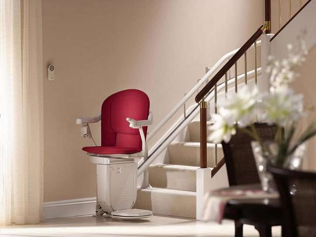 An oblique angle view of the Stannah 260 series Sofia stair lift with red upholstery shown parked at the bottom of the stairs, with the armrests, seat, and footrest all in the down position.