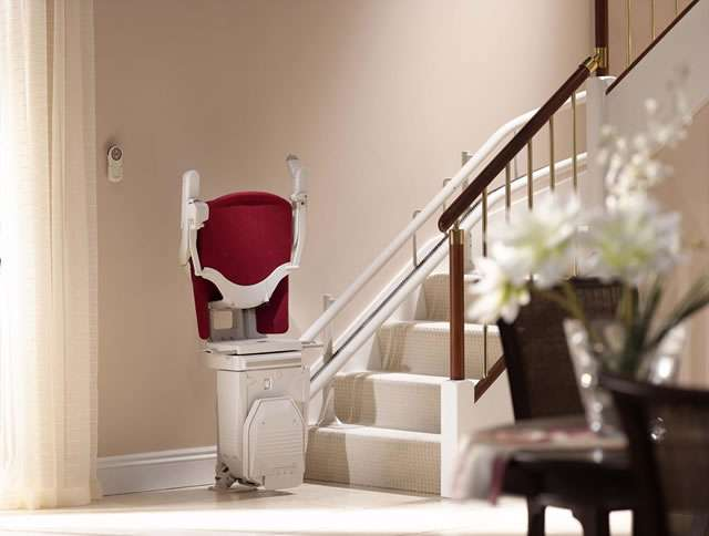 An oblique angle view of the Stannah 260 series Sofia stair lift with red upholstery shown parked at the bottom of the stairs, with the armrests, seat, and footrest all in the up position.