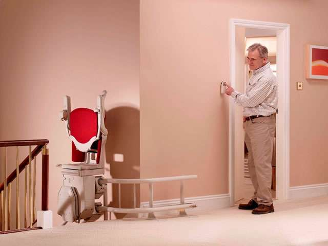 A male user operating the buttons on a wireless remote control situated in a wall-mounted caddy to move the stair lift up or down the stairs.