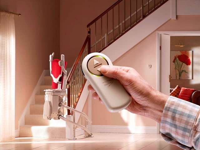 A male user operating the buttons on a wireless remote control held in the hand pointed at the stairlift to move the stair lift chair up or down the staircase.