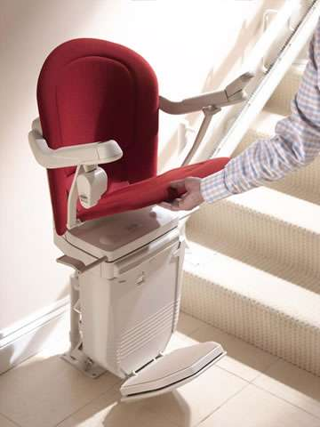 A male user lifting the seat of a Stannah 260 series Sofia stairlift with red upholstery. Because the armrests and footrest are linked internally to the stairlift seat, as the seat is moved, the arm rests and foot rest also move to match.