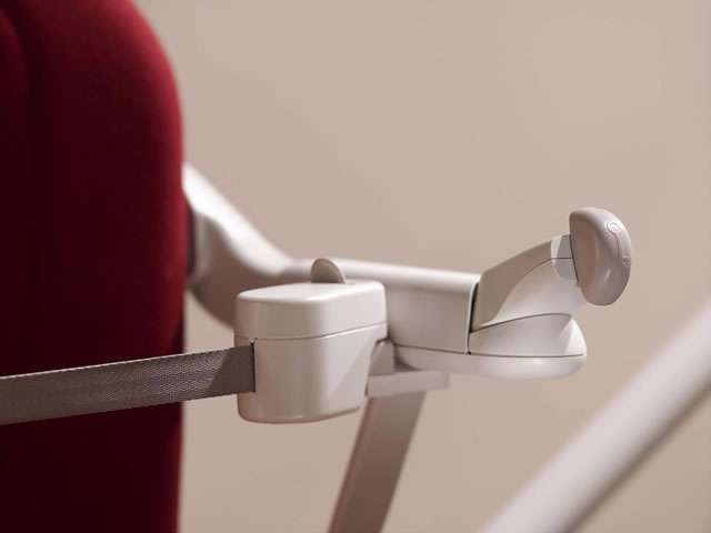 Close-up view of red Stannah 260 series Sofia stair lift with seat belt in closed position and arm rest control turned 90 degress.