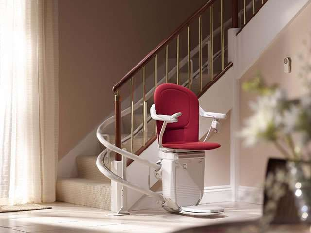 Photo of Stannah 260 series Sofia stairlift with red upholstery, shown parked at the bottom of the stairs around the final curve, with arm rests, seat, and footrest all in the down position, ready to use.