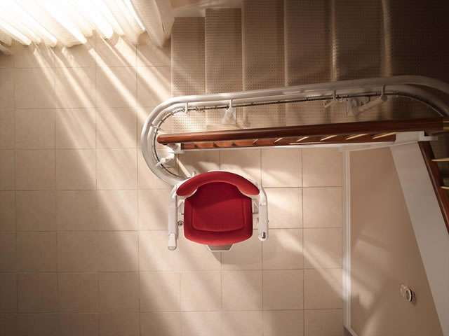 Bird's eye view looking down the curved stairs to directly on top of the Stannah 260 series Sofia stairlift with red colour upholstery.